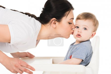 young woman kissing little son in highchair isolated on white background