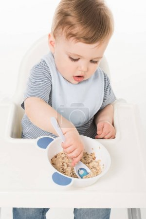 Photo for High angle view of baby boy in bib eating and sitting highchair isolated on white background - Royalty Free Image