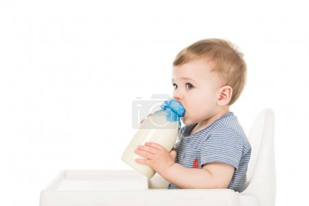 baby boy with bottle of milk and sitting highchair isolated on white background