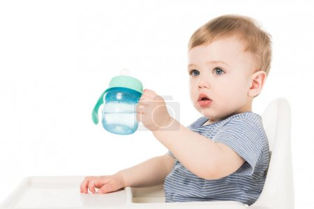 adorable little boy holding baby cup with water and sitting in highchair isolated on white background