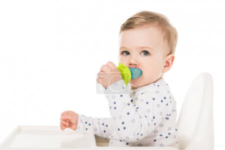 little boy with baby pacifier sitting in highchair isolated on white background