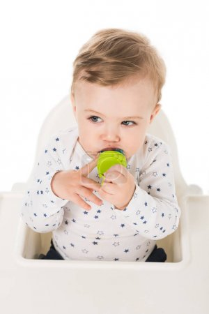high angle view of little boy with baby pacifier sitting in highchair isolated on white background
