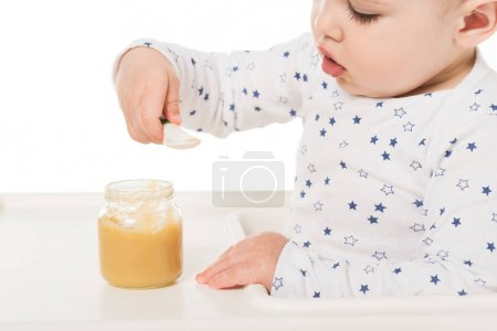 baby boy eating puree from jar and sitting in highchair isolated on white background
