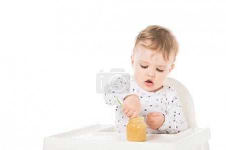 Photo pour Petit garçon manger purée de bocal et assis dans une chaise haute isolé sur fond blanc - image libre de droit