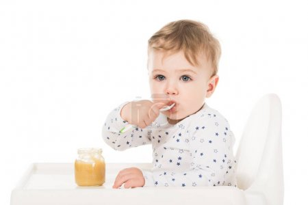 adorable baby boy eating puree from jar and sitting in highchair isolated on white background