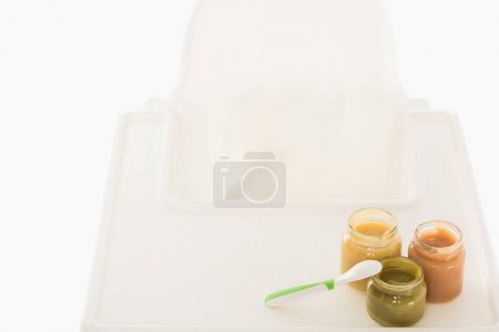 high angle view of three jars with child puree and spoon on highchair isolated on white background