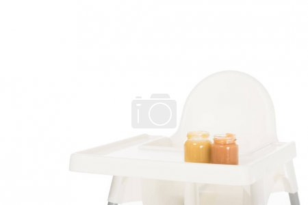closeup shot of two jars with child puree on highchair isolated on white background