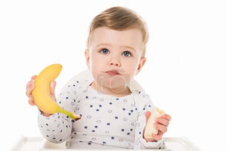 Photo for Little boy with bananas sitting in highchair isolated on white background - Royalty Free Image