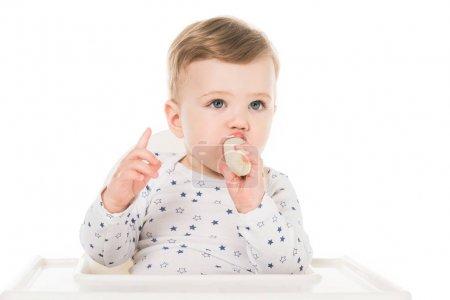 Photo for Baby boy with raised finger eating banana isolated on white background - Royalty Free Image