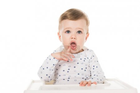 Photo for Adorable little boy sitting in highchair isolated on white background - Royalty Free Image