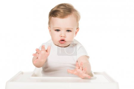 little boy sitting in highchair isolated on white background