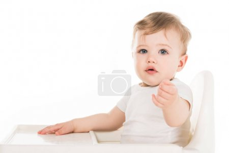 adorable little boy sitting in highchair isolated on white background
