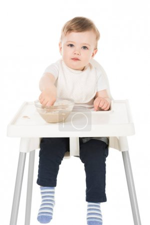 little boy in bib eating puree and sitting in highchair isolated on white background