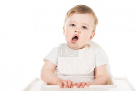 yawning baby boy in bib sitting in highchair isolated on white background