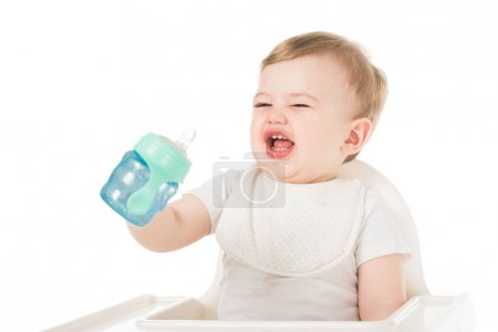 crying little boy in bib holding baby cup and sitting in highchair isolated on white background