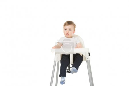 baby boy in bib sitting in highchair isolated on white background