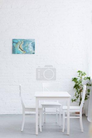 Photo pour Table vide dans un appartement lumineux confortable avec peinture abstraite sur le mur - image libre de droit