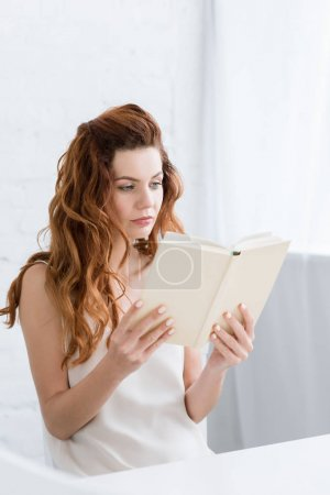concentrated young woman reading book at home