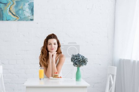 Photo for Beautiful young woman with orange juice and pancakes with strawberry for breakfast at home looking at camera - Royalty Free Image