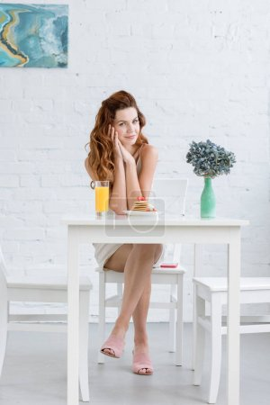 attractive young woman with orange juice and pancakes with strawberry for breakfast at home