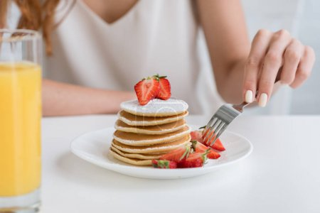 cropped shot of woman having pancakes with strawberry for breakfast
