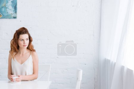 Photo for Thoughtful young woman with cup of coffee in front of white brick wall looking at window - Royalty Free Image