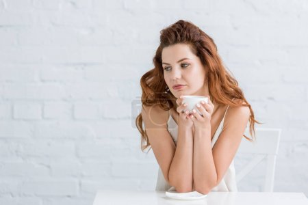 thoughtful young woman with cup of coffee in front of white brick wall