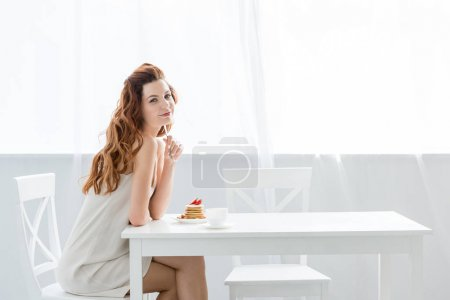 beautiful young woman sitting at table with strawberry pancakes at home