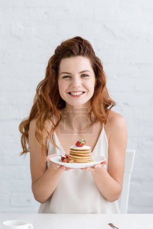 beautiful young woman holding delicious pancakes on plate and looking at camera