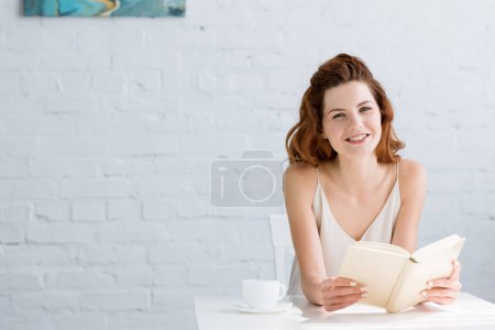Photo for Smiling young woman reading book with coffee cup on table at home - Royalty Free Image
