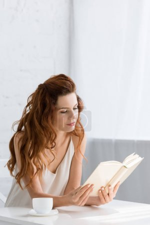 beautiful young woman reading book with coffee cup on table at home
