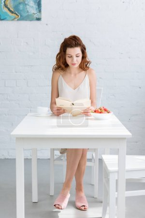 beautiful young woman reading book in morning with coffee and strawberry on table at home