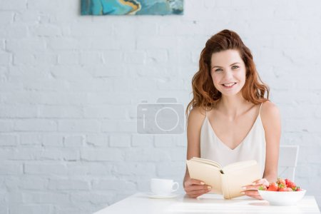 happy young woman sitting at table with coffee and strawberry and reading book at home