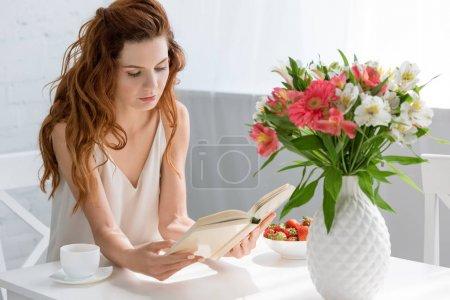 Photo pour Concentré jeune femme lecture livre tandis que assis à la table avec tasse à café et fleurs dans un vase - image libre de droit