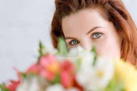 close-up shot of beautiful young woman peeking behind flowers bouquet and looking at camera