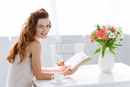 happy young woman reading book while sitting at table with coffee cup and flowers in vase
