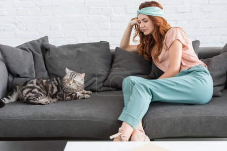 attractive young woman sitting on couch with tabby cat