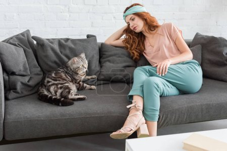 beautiful young woman sitting on couch with tabby cat
