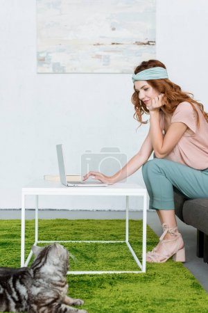 side view of beautiful young woman working with laptop while her cat lying on floor at home