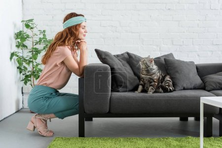 smiling young woman looking at her tabby cat while he sitting on couch at home