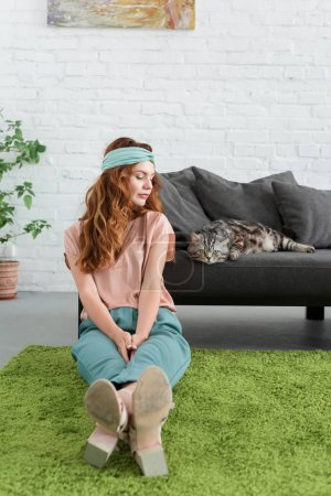 beautiful young woman sitting on floor near her tabby cat at home
