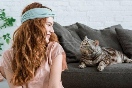 Photo pour Belle jeune femme souriant à adorable chat tabby à la maison - image libre de droit