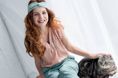 smiling young woman petting adorable tabby cat while sitting on windowsill