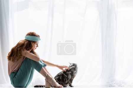 beautiful young woman petting adorable tabby cat while sitting on windowsill