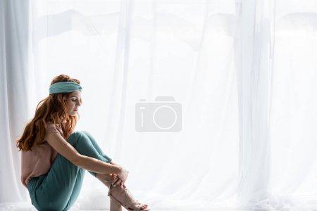 Photo pour Belle jeune femme assise sur le rebord de la fenêtre seule - image libre de droit