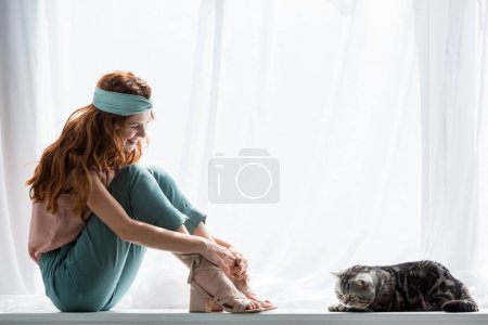 attractive young woman sitting on windowsill with tabby cat