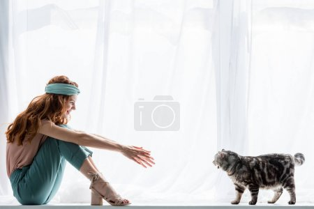 happy young woman sitting on windowsill with tabby cat