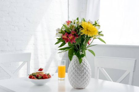 Photo for Delicious pancakes with strawberries and flowers in vase on table - Royalty Free Image