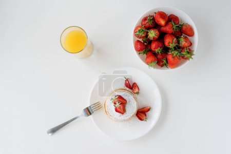 top view of tasty pancakes with strawberries and orange juice