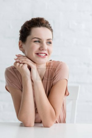 happy young woman sitting at table in front of white brick wall